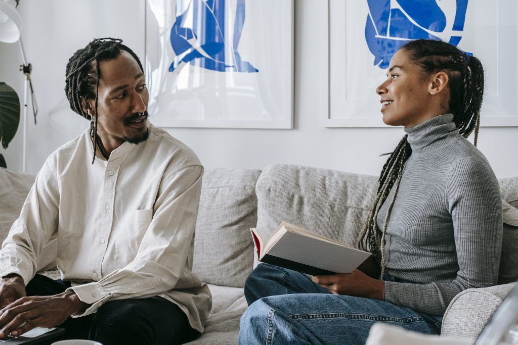 Happy young ethnic couple chatting while sitting on couch at home